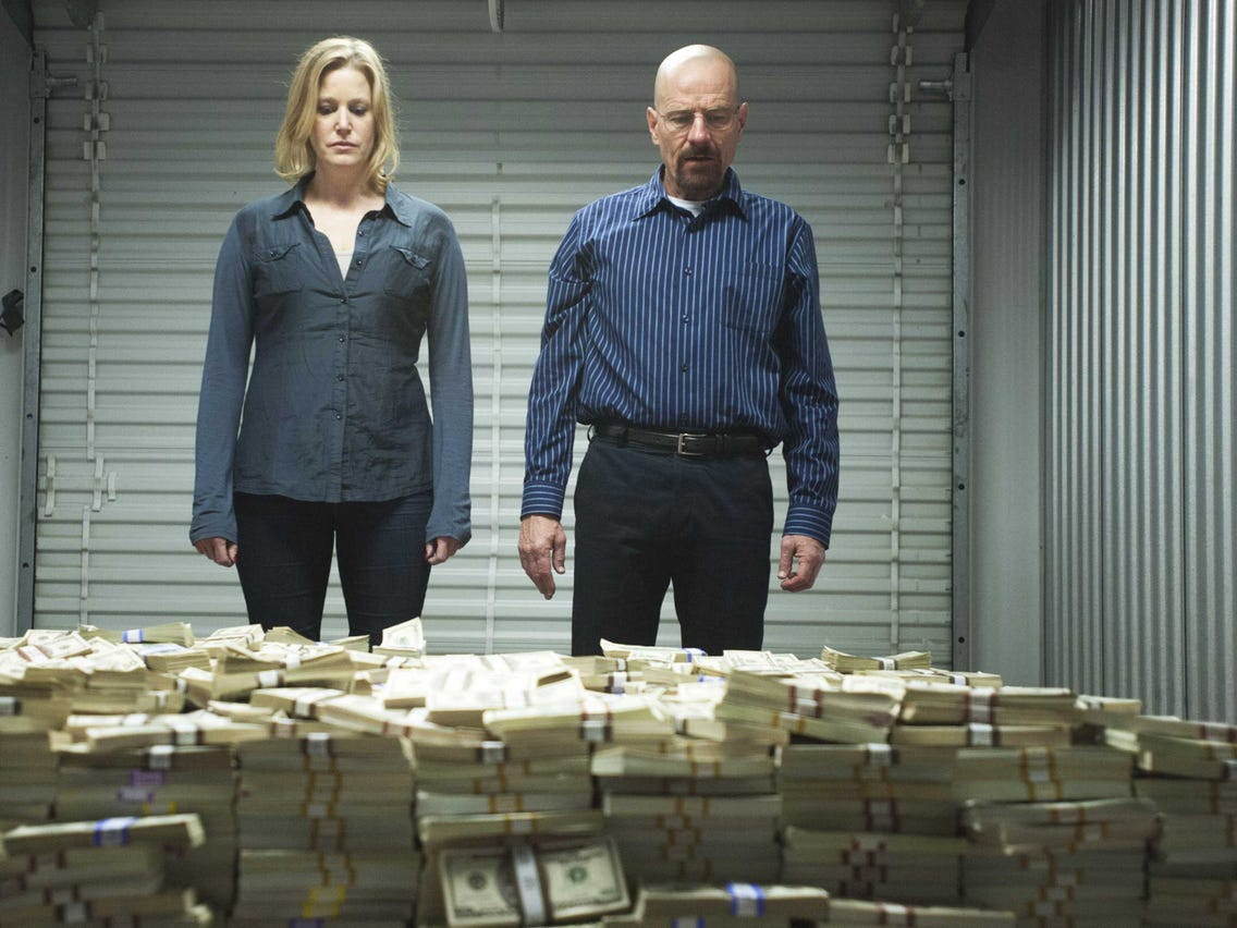 walter white standing with his wife by a money pile